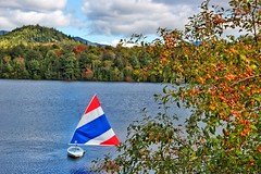 Lake Placid  - New York - Sail Boat  - Red Blue and White (Onasill ~ Bill Badzo) Tags: hospital trudeau road bridge fall autumn collors reflections river dam newyork state staint st armand clintoncounty vacation travel hiking trekking sky clouds hdr tourist leaves turning fishing flyfishing boating town village adirondack mountains landscape seascape winter olympics canon eos rebel 18250mm macro sigma lens sl1 wood tree forest snow mountain mirrorlake lakeplacid colours season lake water boat grass