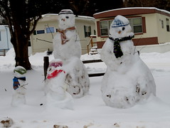 Bedraggled snow family at the trailer court (yooperann) Tags: snowmen family four snow cold trailer housing marquette upper peninsula michigan