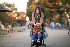 Portrait of young mother and little son in public park at sunset (Apricot Cafe) Tags: img116741 asia asianandindianethnicities canonef85mmf14lisusm japan japaneseethnicity millennialgeneration mitakatokyo tokyojapan autumn babystroller backlit bonding boys candid carefree casualclothing child colorimage day family footpath fulllength happiness inokashirapark kichijoji leisureactivity lifestyles lookingatcamera mother outdoors peacesign people photography portrait publicpark realpeople sitting smiling son straighthair street sunlight sunset togetherness toothysmile twopeople weekendactivities women youngadult