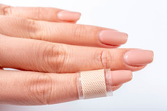Plaster glued on the finger of a woman (wuestenigel) Tags: protection treatment accident pain injury doctor emergency help fix assistance aid adhesive cure band finger bandage medicine plaster first care hand patch patient health recovery skin medical wound white haut woman frau behandlung gesundheit fingernail fingernagel healthcare gesundheitswesen hilfe manicure maniküre medizin die thumb daumen human mensch schmerzen palmhand handfläche isolated isoliert detail body karosserie nail nagel