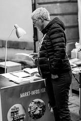 A Closer Look (Isengardt) Tags: look anschauen closer nah blick lamp lampe woman frau people leute menschen street strase streetphotography strasenfotografie broschüre stand auslage black white schwarz weiss monochrome monochrom advent adventsmarkt christmas christmasmarket weihnacht weihnachtsmarkt esslingen badenwürttemberg deutschland germany europe europa canon eos 550d 50mm