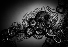 the beauty of going in circles (Reflectory (Chris Brown)) Tags: abstract abstraction nopeople horizontal landscape monochrome blackandwhite bw black white gray lowkey circles curves ellipses ovals loops slinky metal coil reflectory