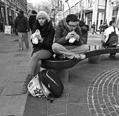 'Comfort break' (Andy WXx2009) Tags: blackandwhite monochrome streetphotography fashion lunch eating fastfood people outdoors candid cardiff wales europe bench sitting bags hats urban woman man girl femme style street jeans shopping crosslegged boots