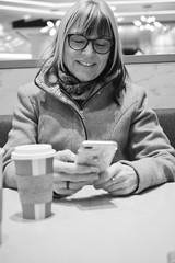 A Rare Monday Smile (flashfix) Tags: november192018 2018inphotos flashfix flashfixphotography ottawa ontario canada nikond7100 40mm portrait mom female phone bokeh texting smile monochrome blackandwhiteportrait blackandwhite