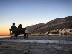 A couple on a bench on Symi (VillaRhapsody) Tags: greece greek symi island daytrip sunset evening waiting dusk people candid bench harbour behind couple romantic challengeyouwinner cyunanimous
