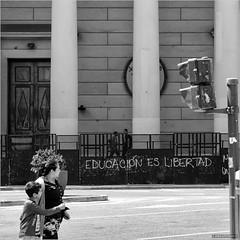 Education is freedom (John Riper) Tags: johnriper street photography straatfotografie square vierkant bw black white zwartwit mono monochrome argentina buenosaires plazademayo ba john riper rotterdam fuji fujifilm xt2 xf 18135 demonstration grafiti boy mother son point metropolitan cathedral