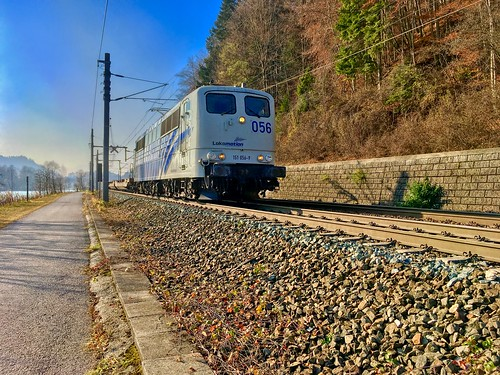 Electric locomotive pulling an empty freight train passing the river Inn near Kufstein, Tyrol, Austria