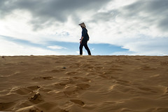 Man standing on Top of a Sand Dune in the Red Sand Dunes of Mui Ne, Vietnam