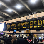 London Euston station departure board during a busy period with lots of people waiting for trains thumbnail