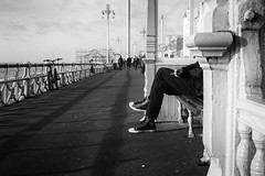 Taking in the view (markfly1) Tags: brighton seafront seascape seaside city man legs cigarette hand lit fag smoking trainers sneakers converse black white candid image railings bench seat sat down bright sunshine harsh sunlight shadows low winter sun streetphoto street promenade nikon d750 35mm manual focus lens