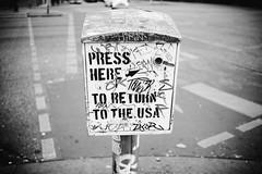 """""""Press here to return to the USA"""" (Eric Flexyourhead) Tags: friedrichshain friedrichshainkreuzberg berlin germany deutschland federalrepublicofgermany bundesrepublikdeutschland city urban detail fragment monochrome blackwhite bw vignette shallowdepthoffield bokeh sonyalphaa7 zeisssonnartfe35mmf28za zeiss 35mmf28"""