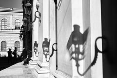 Chatting (iamunclefester) Tags: münchen munich street blackandwhite monochrome autumnstreetphotos bayerischestaatsoper opera castshadow hardshadow lantern light lights facade chat conversation