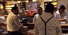 Kitchen Confidential (MPnormaleye) Tags: men group conversation relaxed intimate cafe restaurant kitchen cuisine utata 35mm lensbaby seeinanewway urban lowlight equipment