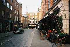 London (goodfella2459) Tags: nikonf4 afnikkor24mmf28dlens kodakektar100 35mm c41 film analog london colour city streets road buildings car cafe chairs people manilovefilm