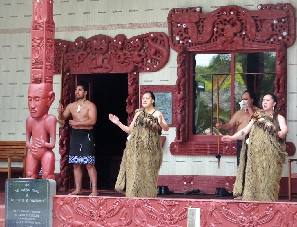 Waitangi. Maori men and women sing for visting tourisst about to enter the Treaty Grounds Marae or meeting house.