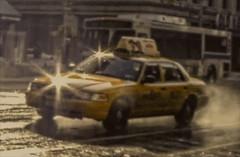 "NYC Yellow Cab Driving and Splashing Thru Sunlit Wet Street (nrhodesphotos(the_eye_of_the_moment)) Tags: dscn40963001084 ""theeyeofthemoment21gmailcom"" ""wwwflickrcomphotostheeyeofthemoment"" streetscene reflections shadows metal glass auto car windows transportation yellowtaxicab mtabus bus street wet sunlit outdoors rainy"