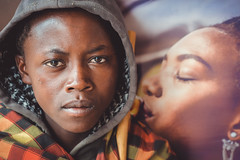 The Kiss (u c c r o w) Tags: maasai africa kiss black african teen teenager kid portre portrait colors colorful urban urbanlife city citylife tanzania tanzanian people hood eyes
