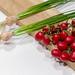 Künstliche ganze Frühlingszwiebeln mit Stängeln und Tomaten an Strauch auf Holzbrett