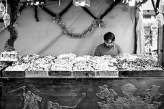 Sweets (fernando_gm) Tags: 35mm fujifilm street streetlife streetart alicante calle monochrome monocromo monocromatico blackandwhite bw blancoynegro people persona man hombre tienda shop sweets golosinas dulces vendedor comerciante altea