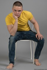 Guy sitting in jeans (StudioLads.com) Tags: male model man guy dude youth stud hunk pose studio photoshoot chair jeans tshirt fashion trendy casual yellow blue hot horny sexy cute foot feet barefoot sit sitting