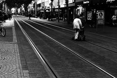 Line crossing (Leica M6) (stefankamert) Tags: lines tram people blur film analog analogue leica m6 leicam6 voigtländer nokton kodak trix blackandwhite blackwhite noiretblanc noir karlsruhe street grain crossing walking
