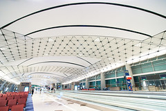 Hong Kong International Airport Gates 1 (ArdieBeaPhotography) Tags: airport gates travellator conveyorbelt rowsofchairs chairs seats clean white glow geometric pattern ceiling arched arcs triangular blue carpet passengers waiting windows night light bright flourescent wideangle