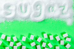 white granulated sugar and refined sugar on a green background with the inscription (wuestenigel) Tags: raw sugar natural dessert granulated closeup cooking cube crystalline texture crystal sugarcane background food macro ingredient delicious pile product refined heap sweet sweetener unhealthy white desktop illustration symbol christmas weihnachten abstract abstrakt shape gestalten noperson keineperson design bright hell paper papier wallpaper tapete color farbe graphic grafik pattern muster textur image bild decoration dekoration art kunst winter business geschäft