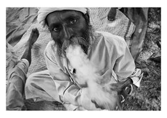 portrait of a head man (handheld-films) Tags: india portrait portraiture male headman man men smoking smoke chillum pipe closeup face exhale smoker indian mono blackandwhite ruralindia rajasthan travel