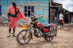 Maasai & The King Lion (u c c r o w) Tags: maasai black tanzania arusha native motorcycle motorbike motosiklet red kenya africa african portrait blue wooden wall colors colorful village cityscape urban urbanlife
