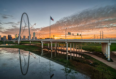 Lone Star State Sunrise (tquist24) Tags: dallas hdr margarethunthillbridge nikon nikond5300 outdoor texas trinityriver bridge city cityscape clouds dawn downtown flag flagpole geotagged longexposure morning reflection reflections river sky skyline sunrise urban water