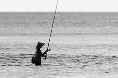 Fishing (PB2_3417) (Param-Roving-Photog) Tags: fishing fisherman asianricehat conical longfishingrod sea ocean water waves quiet still serene padangpadang beach bali indonesia streetphotographer travelphotography wanderer rovingphotog parambhogal candid monochrome blackandwhite bw
