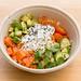 Vitaminreiche Ernährung mit rohen Lachsstücken, Avocado, Gemüse, Kräutern und Samen