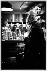 Girl at the bar (Adeypoos) Tags: girl candid streetlevelphoto street stphotographia streettogs streetphotography straatfoto streetfoto contrast bw blackandwhite beautiful bokeh bobblehat phone texting backlight