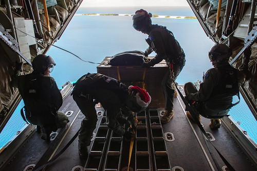 Royal Australian Airmen prepare a bundle to be airdropped to the atoll of Kapingamarangi during OCD