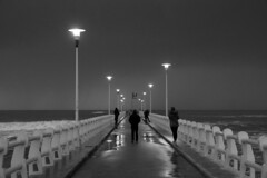 Walking on the bridge in a cloudy afternoon (Darea62) Tags: people blackandwhite streetlights sea wet fortedeimarmi versilia tuscany pier jetty bw landscape panorama architecture mood