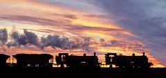 Two 10 Class roll towards Mt Dee, silhouetted against the fiery evening sky. June, 1979 . (garratt3) Tags: aus film pentax rail railroad steam smr sunset 10class newsouthwalescoaltrains southmaitlandrailway nswcoaltrains standardgauge steamloco railway railways locomotive australia kodachrome railfan steamlocomotive steampower newsouthwales