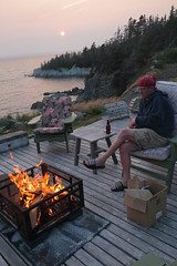 Evening Burn (peterkelly) Tags: digital canon 6d northamerica canada newfoundlandlabrador cavendish sunset water trinitybay shore shoreline coast coastline evening dusk fire hot lit bonfire deck chair man bandana table beer forest trees wood wooden lobstertrap flames flame sun