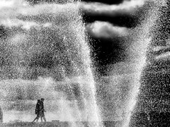 Keep walking: ignore the spray! (Cassiezee) Tags: black white grey water fountain spray people walking clouds