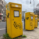 Three yellow mailboxes of the German post painted with graffiti at intersection thumbnail