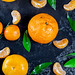 Fresh mandarin oranges fruit with leaves on dark table