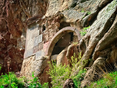 Church carved into the rock (Tigra K) Tags: goght kotayk armenia am 2006 architdetail architecture carving church cross geghard grass medieval nature ornament plant portal rock ruin wall art arch