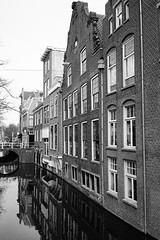 Historic Delft in monochrome (Eric Flexyourhead) Tags: voldersgracht delft zuidholland southholland netherlands holland nederland city urban canal oldtown historic building buildings houses brick monochrome blackwhite bw sonyalphaa7 zeisssonnartfe35mmf28za zeiss 35mmf28