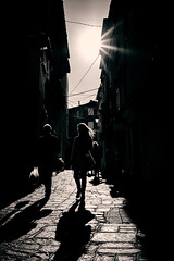 Shopping time (iamunclefester) Tags: vacation holiday croatia krk otokkrk baška shopping time backlight couple silhouette castshadow hardshadow shadow shadows alley alleyway cable street light lamp lantern bag glow cobblestone town bright sunny sun halo toned autumnbacklightseries lowsun
