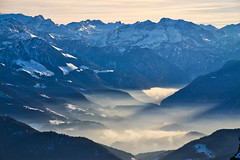 Haze and wisps of fog below the Berchtesgaden Alps (echumachenco) Tags: mountain mountains mountainside mountainrange alps outdoor landscape winter december snow valley haze fog berchtesgadenerland berchtesgadeneralpen steinernesmeer berchtesgaden schönau königssee view panorama untersberg bavaria bayern germany deutschland nikond3100 inversionweather sky