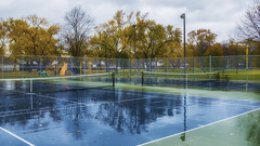 Reflections On A Tennis Court. Windsor, ON. (Paul Thibodeau) Tags: photooftheday windsor fujifilmx100f centralpark tennis courts reflections trees autumn fall colours