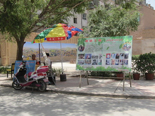 "Two officials at a booth to advise locals on ""extremist"" appearances.  Kashgar, Xinjiang, China"