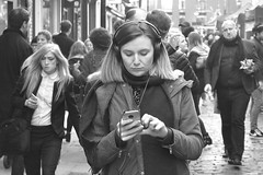 Got to look where you're going.... (markwilkins64) Tags: london struttonground victoria uk streetphotography streetscene streetstory street streetphoto mono blackandwhite bw mobilephone headphones texting walking concentration markwilkins mark concentrating crowd