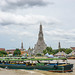 Boat with Tourists driving past Wat Arun Temple on Chao Phraya River in Bangkok