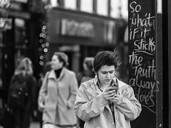 Searching for truth (Frank Fullard) Tags: fullard candid street portrait search truth quest cork notice irish ireland lady mobile phone internet monochrome black white blanc noir online dilemma question