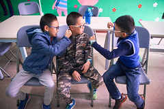 2019 Winter Camp Classroom Kids 12 (ArdieBeaPhotography) Tags: three boys classroom trio expresive silly funny feelings emotions chairs table tile floor wallmural drinkbottle waterbottle glasses watch camo pullover sweatervest anorak parka raincoat sweats jeans trainers faces grins teeth young preteen friends class foolingaround tamronspaf2875mmf28xrdildasphericalif